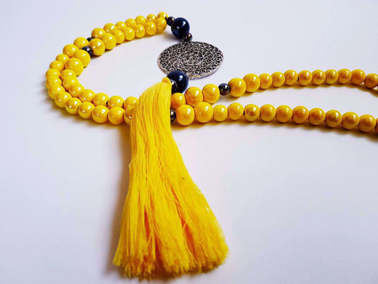 Picture of Woman's Necklace with yellow ceramic beads, a silver colored metal  pendant and big tassel ending. Handmade