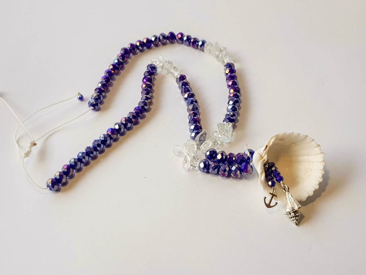 Picture of Woman's Necklace with crystal beads, transparent chips, metallic elements and a big natural seashell. Handmade.