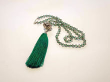 Picture of Woman's Necklace with transparent crystal beads, big metallic element and big green tassel ending. Handmade