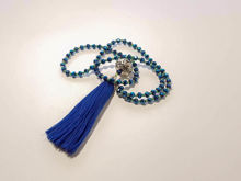 Picture of Woman's Necklace with a combination of blue and petrol blue  crystal beads, big metallic element and a big blue tassel ending. Handmade