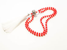 Picture of Woman's Necklace with a combination of reg and frosty white  crystal beads, big metallic element and a big white tassel ending. Handmade