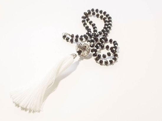 Picture of Woman's Necklace with a combination of black and white  crystal beads, big metallic element and a big white tassel ending. Handmade