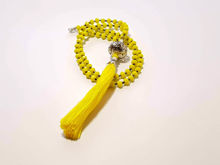 Picture of Woman's Necklace with yellow crystal beads, big metallic element and a big yellow tassel ending. Handmade