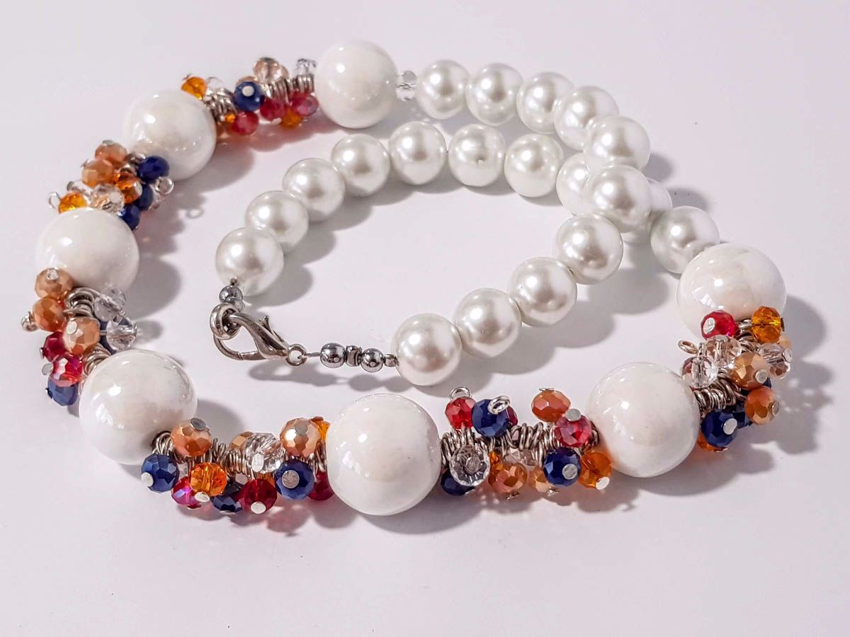 Picture of Woman's Necklace with a combination  of white ceramic beards and various colors of crystal beads in an grape like shape . Handmade