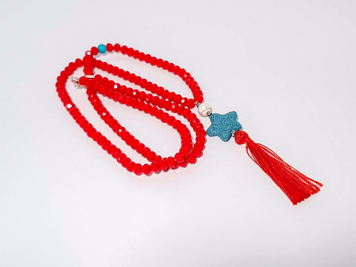 Picture of Woman's Necklace with a combination  of red crystal beards, a white chaolite bead, a green lava stone pendant and a big red tassel  ending. Handmade