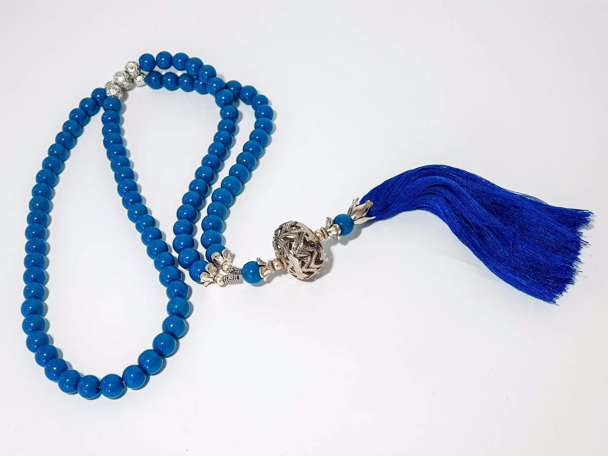 Picture of Woman's Necklace with blue onyx beads, silver lava stones a metal element and big blue tassel ending. Handmade