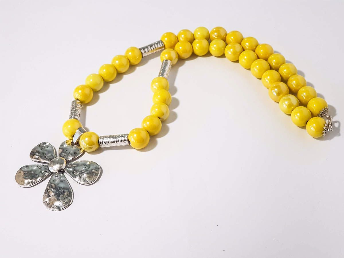 Picture of Woman's Necklace with a combination of yellow ceramic beads, metallic elements and a big metallic star pendant. Handmade